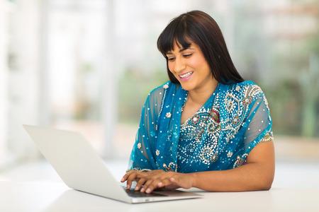 mujer elegante: feliz mujer india joven que usa el ordenador en casa