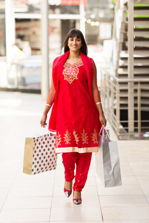 happy indian woman carrying shopping bags walking in mall photo