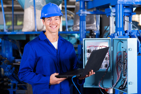 electronics equipment: portrait of happy industrial engineer with laptop computer Stock Photo
