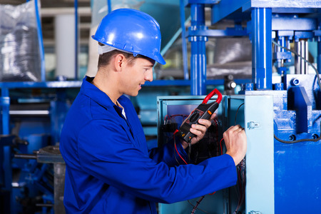 industrial technician examining control box with digital insulation tester