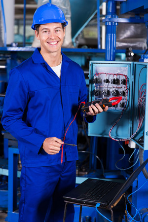 young plant: handsome male technician holding digital insulation tester Stock Photo