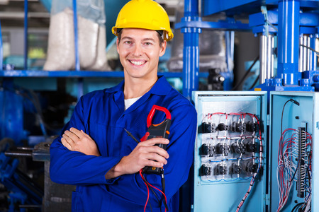 happy electrician holding digital insulation resistance tester Stockfoto