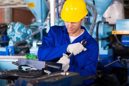 fasten: skilled factory mechanic using spanner fasten gumboot making machine