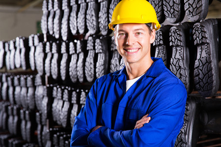 rubber sole: handsome gumboots factory worker with arms folded