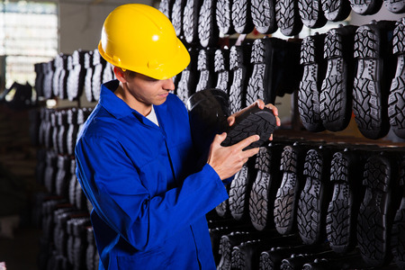 quality controller: quality controller checking rubber-boots sole in storeroom