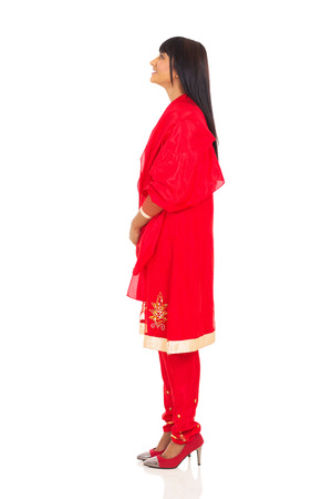 young indian woman in red saree looking up photo