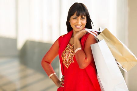cheerful indian young lady shopping in mall