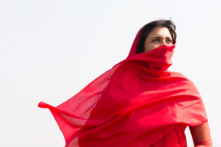 cultural clothing: thoughtful indian woman in sari covering her face with veil