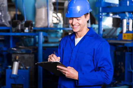 hard worker: happy factory worker writing report