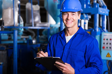 factory machine: male industrial technician working inside a factory Stock Photo