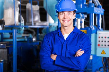 overol: alegre trabajador de una fábrica joven con los brazos cruzados
