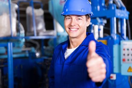 overol: alegre trabajador pulgar en fábrica Foto de archivo