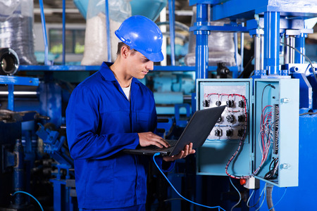 industrial programmer checking control box status with laptop computer Stock Photo