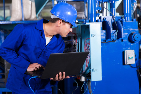 hard worker: industrial technician checking distribution box with laptop in factory Stock Photo