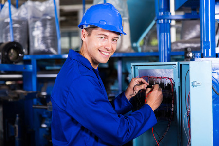 happy male electrician working on industrial machine Standard-Bild