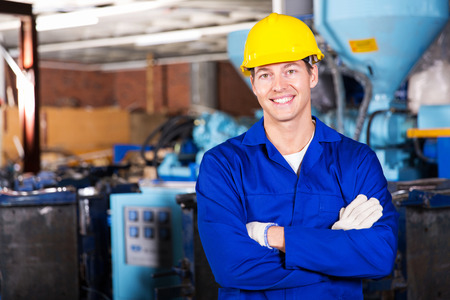 manufacturer: good looking blue collar worker in factory Stock Photo