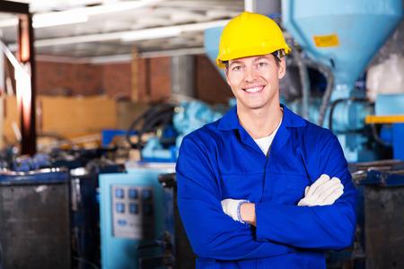 good looking blue collar worker in factory Standard-Bild