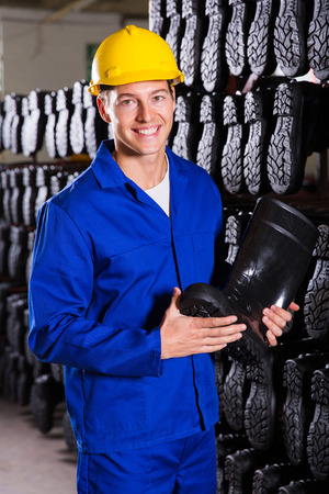 smiling factory worker holding rubber-boot photo