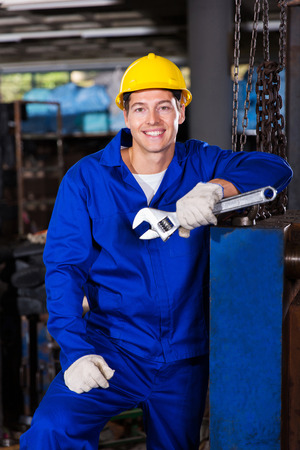 male manual worker holding spanner in factory photo