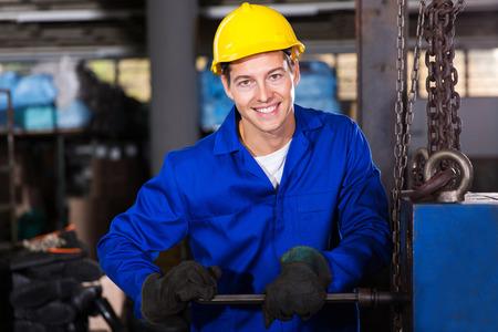 blue steel: happy repairman fixing machine inside the factory Stock Photo