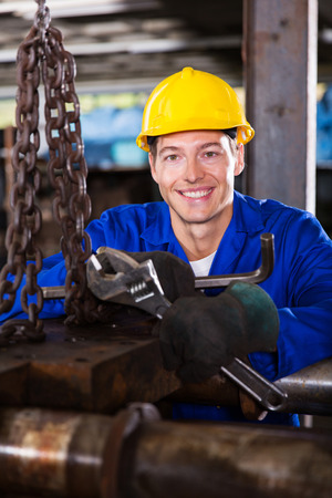 happy young male industrial mechanic at work photo