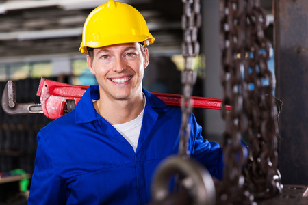 steel plant: industrial worker carrying monkey wrench in workshop