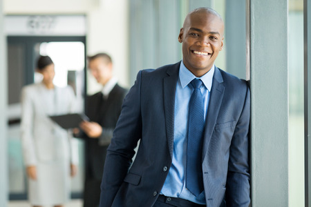 manager office: portrait of young african businessman with colleagues on background Stock Photo