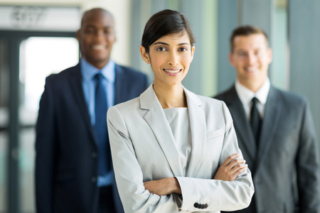 beautiful female business leader with team standing on background photo