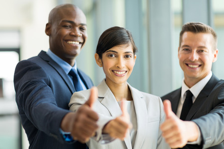 looking up: happy business group giving thumbs up Stock Photo