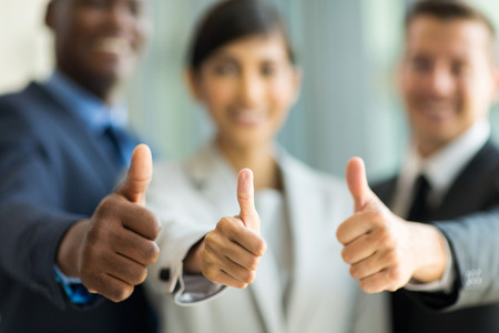 close up of multiracial business team giving thumbs up