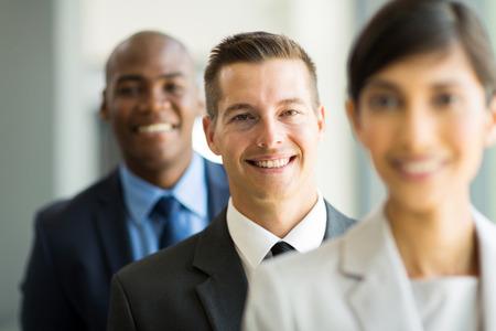 fila de personas: joven hombre de negocios feliz de pie en una fila con sus colegas Foto de archivo