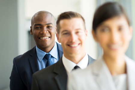 african businessman: happy african businessman standing in a row with colleagues Stock Photo