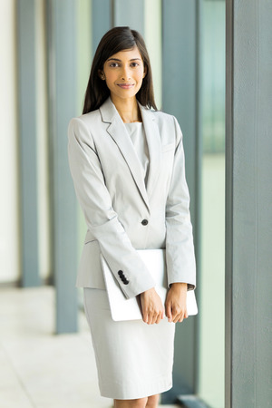 pretty indian businesswoman holding laptop in office photo