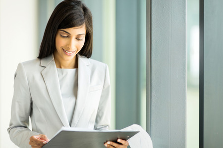 successful indian businesswoman reading monthly report photo