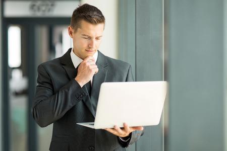 Apuesto hombre de negocios la lectura de correo electrónico en su computadora portátil Foto de archivo - 33190690