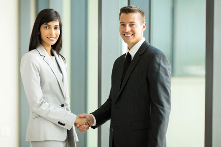 indian business man: happy business partners handshaking in conference hall