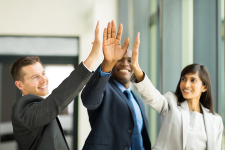 by hand: happy business team giving high five in office Stock Photo