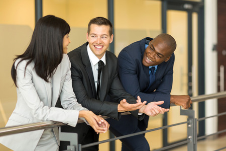 fun at work: businessman having fun conversation with colleagues during break