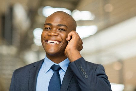 cheerful african american businessman talking on cell phone photo