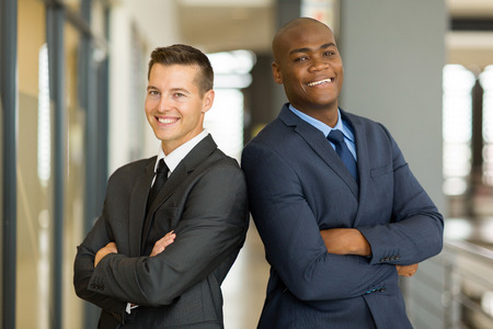 co work: cheerful young businessmen with arms crossed in office