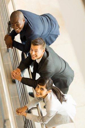 co workers: overhead view of happy businesspeople looking up