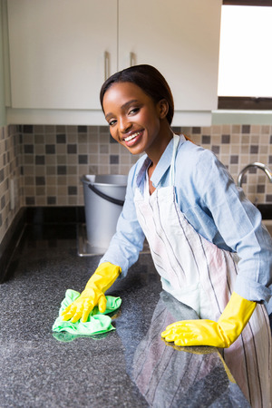 house chores: happy young african woman cleaning kitchen counter Stock Photo