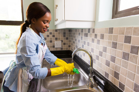 chores: beautiful african american woman doing house chores Stock Photo