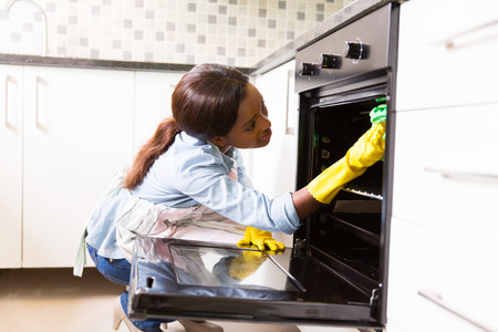 Domestic cleaning: african woman cleaning stove in the modern kitchen Stock Photo