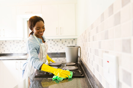 kitchen aprons: smiling african woman cleaning the stove