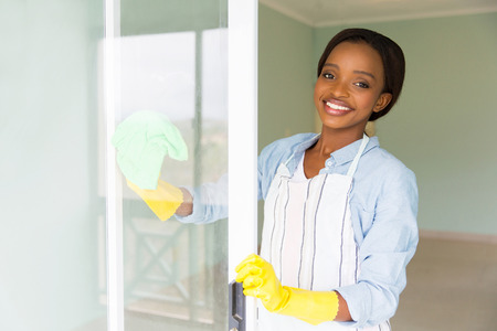 happy black woman: portrait of african housewife cleaning a door glass Stock Photo