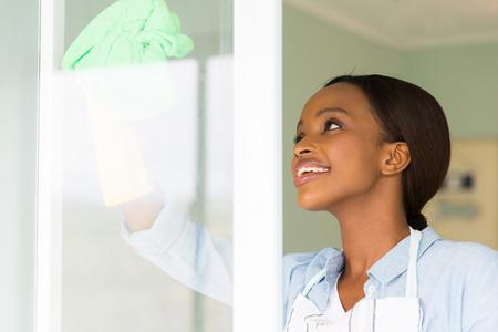 gospodarstwo domowe: ładna kobieta czyszczenia okien afrykański z tkaniny szklanej Zdjęcie Seryjne