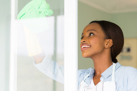 pretty african woman cleaning window glass with cloth