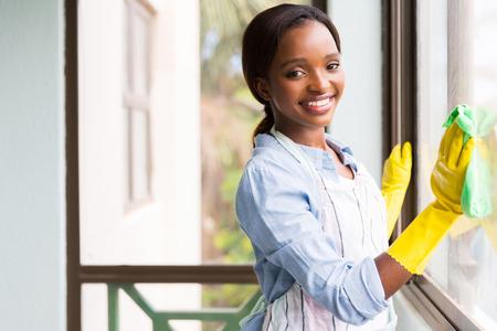 mujer limpiando: atractivo africano ventana de cristal de limpieza chica Foto de archivo