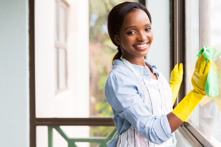the window: attractive african girl cleaning window glass